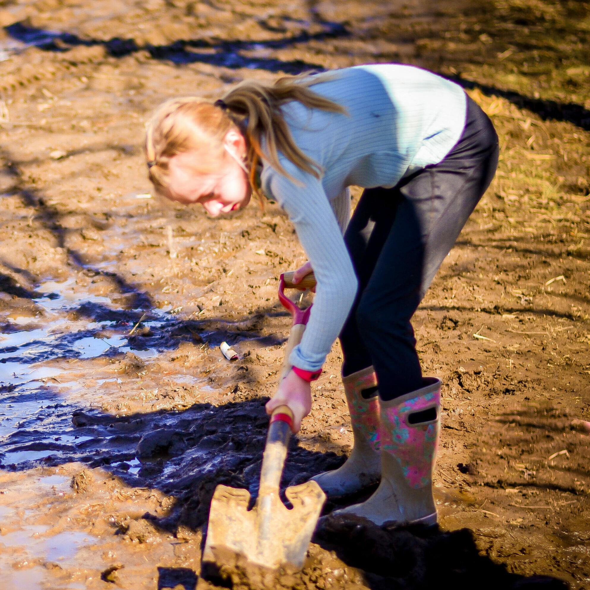 Student shoveling mud